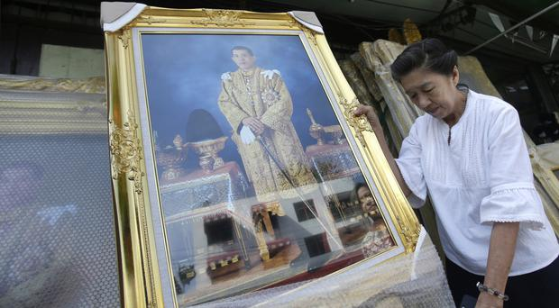 A shopkeeper places portraits of Thailand's Crown Prince Vajiralongkorn outside her shop in Bangkok (AP)