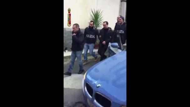 Italian Police escort Marcello Pesce, third right, to a vehicle in Rosarno (AP)