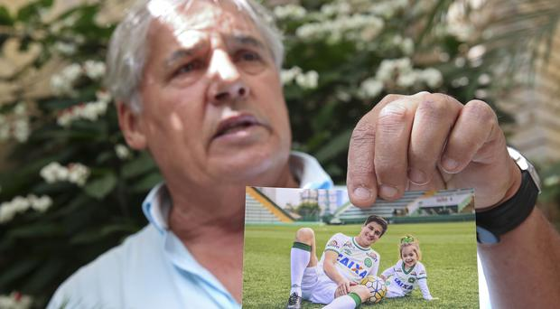 Osmar Machado holds a picture of his son Filipe, who died in the crash and grand-daughter Antonella (AP)