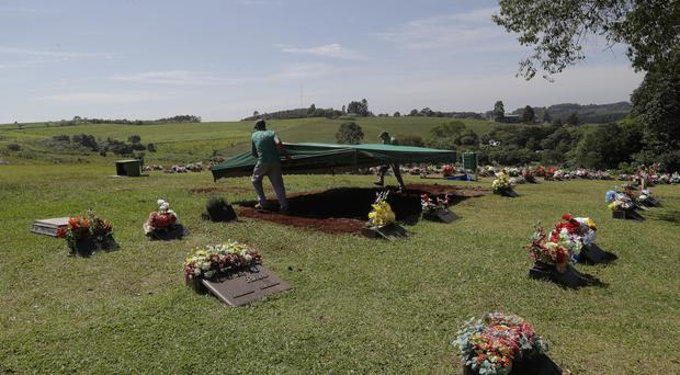 Cemetery workers prepare burial sites in Chapeco, Brazil, as Colombia begins repatriating the dead from a plane crash (AP)