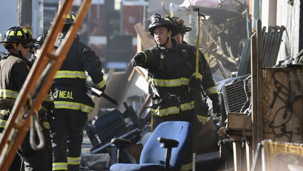 Firefighters assess the scene of the deadly fire (AP)