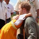 A hug for Prince Harry from a young resident of Sumara Village in Guyana