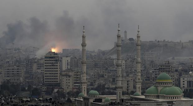 Fire rises following a Syrian government air strike that hit rebel positions in eastern Aleppo (AP)