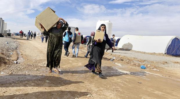 Iraqis who fled the fighting between security forces and Islamic State militants carry humanitarian aid (AP)