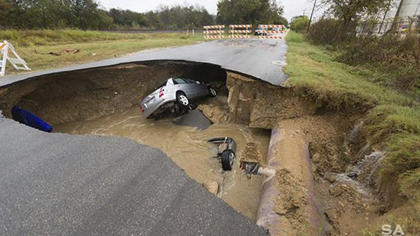 Cars trapped in a sinkhole in San Antonio (San Antonio Fire Department/AP)