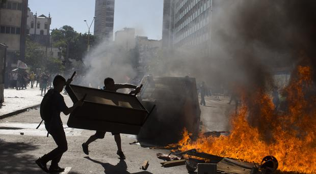 Demonstrators set a roadblock on fire outside the state legislature in Rio de Janeiro (AP)