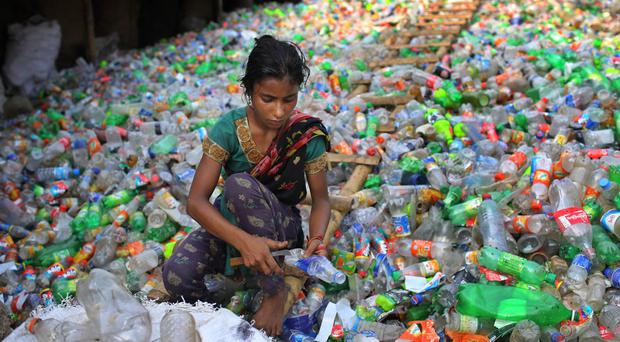 Bangladeshi girl Sefaly, 13 years old, removes labels and caps from plastic bottles as she works at a recycling factory in Dhaka, Bangladesh.