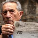 Holocaust survivor Adolf Burger holds up one of his original bank notes at a press call for the film The Counterfeiters