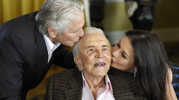 Kirk Douglas gets a kiss from his son Michael Douglas and daughter-in-law Catherine Zeta-Jones (Invision/AP)