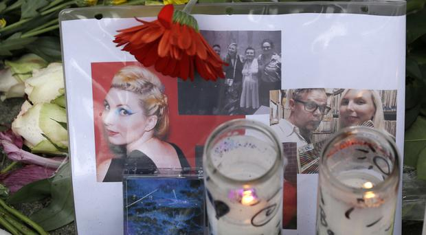 Candles burn next to a group of photographs at a makeshift memorial near the site of the Ghost Ship warehouse fire in Oakland, California (AP)