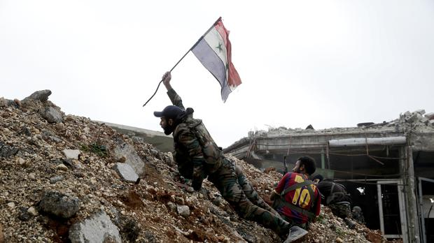 A Syrian army soldier places a Syrian national flag during a battle with rebel fighters at the Ramouseh front line, east of Aleppo (AP)