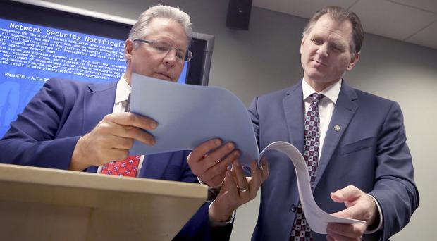 Wisconsin Elections Commission chairman Mark Thomsen, left, and commission administrator Michael Haas scan the results of the recount in Wisconsin (Wisconsin State Journal/AP)