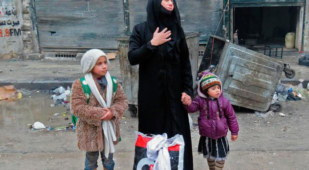 A Syrian woman cries as she leaves the city with her children