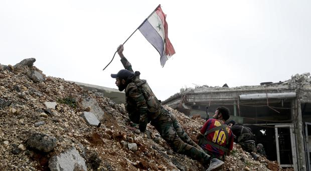 A Syrian soldier plants the national flag during a battle with rebel fighters east of Aleppo (AP)