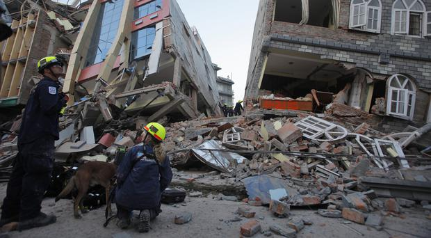 Rescue workers inspect the site of collapsed buildings in Kathmandu after last year's devastating earthquake