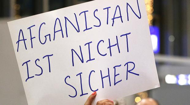 A demonstrator holds a sign reading 'Afghanistan is not safe' during a protest against the deportation of 50 Afghan asylum seekers at Frankfurt airport (AP/Michael Probst)