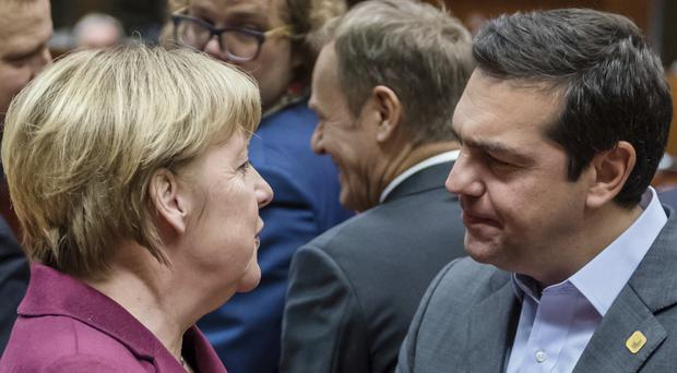Greek prime minister Alexis Tsipras talks to German chancellor Angela Merkel at the EU summit in Brussels (AP)