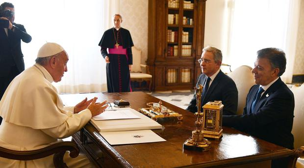 Pope Francis talks to Colombian President Juan Manuel Santos and former President Alvaro Uribe during a meeting at the Vatican. (Vincenzo Pinto /AP)