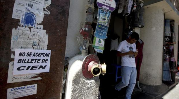 A shop displays a message posted in Spanish:
