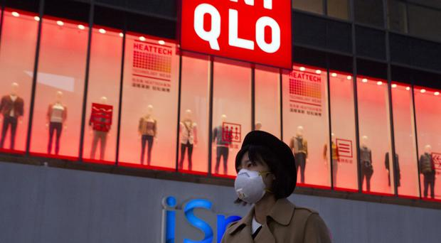 A woman wears a mask to protect herself from pollution in Beijing, China (AP)