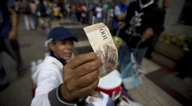 A street vendor inspects the authenticity of a 100-bolivar note as people queue outside a Caracas bank (AP)