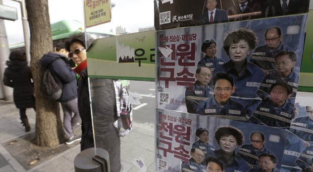 Posters showing portraits of impeached South Korea's President Park Geun-hye, her aides and businessmen at a bus station in Seoul, South Korea (AP)