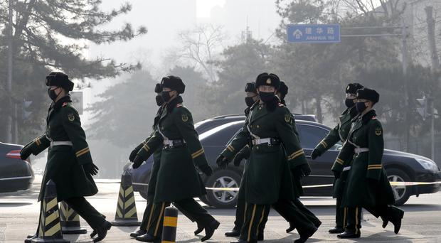 Chinese paramilitary policemen wearing masks for protection against pollution as the capital , Beijing, is shrouded in smog (AP)