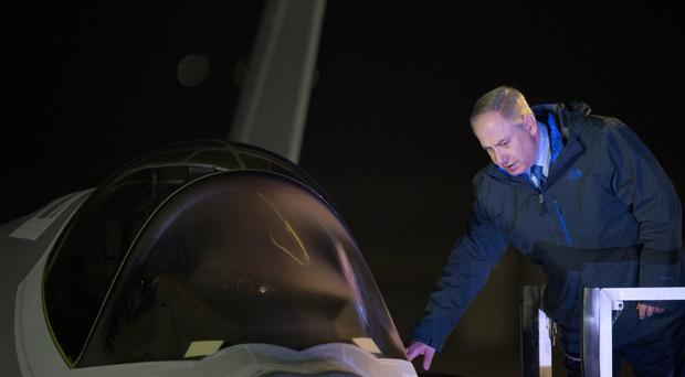 Israeli prime minister Benjamin Netanyahu reaches to one of the first two next-generation F-35 fighter jets after it landed during an unveiling ceremony upon arrival in Nevatim Air Force base near Beersheba (AP)