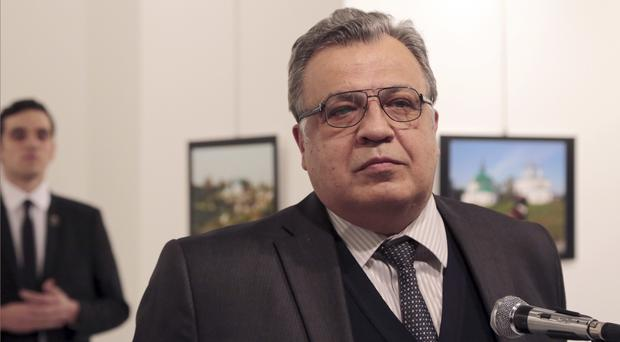 Andrei Karlov, the Russian Ambassador to Turkey, speaks at a photo exhibition in Ankara moments before a gunman opened fire on him (Burhan Ozbilici/AP)