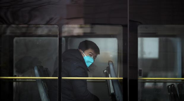 A man wearing a mask for protection against air pollution looks out from a bus in Beijing (AP)