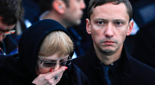 Grief: Marina, wife of Andrei Karlov, mourns as her husband's body is brought home to Russia