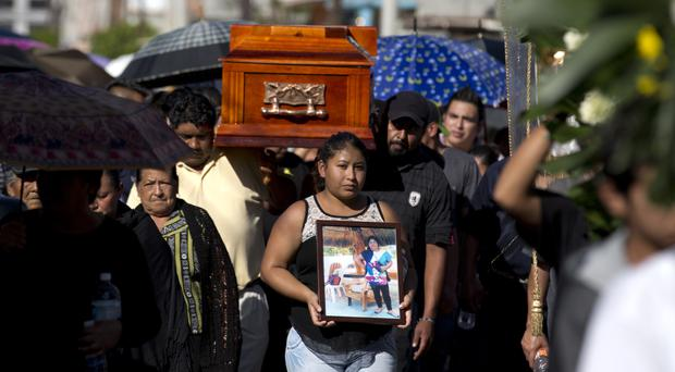 A woman walks with a photo of Martina Almazan in front of the coffin that contain her remains, in Tultepec (AP)