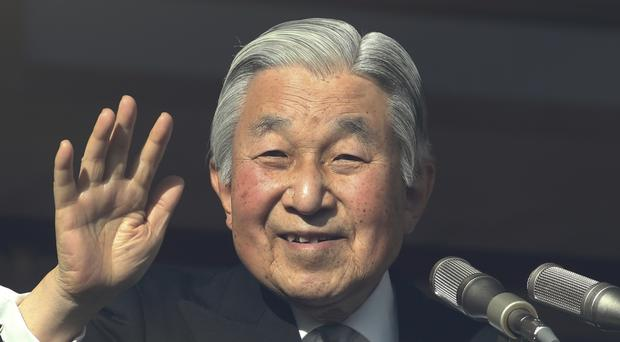 Japan's Emperor Akihito waves as he appears on the bullet-proofed balcony of the Imperial Palace in Tokyo to mark his 83rd birthday (AP/Koji Sasahara)
