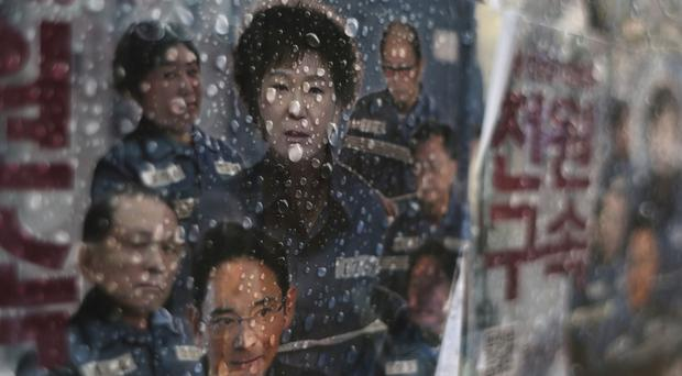 A poster showing portraits of Park Geun-hye, Choi Soon-sil and Lee Jae-yong, a vice chairman of Samsung, is displayed in Seoul (AP/Lee Jin-man)