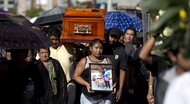 A woman walks with a photo of Martina Almazan in front of the coffin that contains her remains (AP)