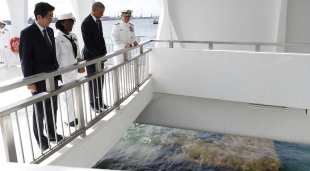 Barack Obama and Shinzo Abe at the USS Arizona Memorial, where the wreckage of the ship can be seen in the water below (AP)
