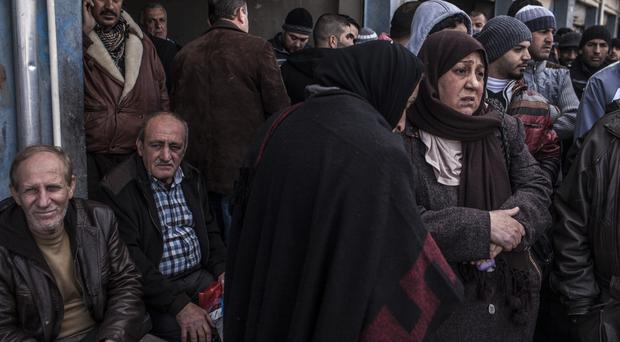 Iraqis who have been displaced from Mosul wait to be transferred to various camps (AP)