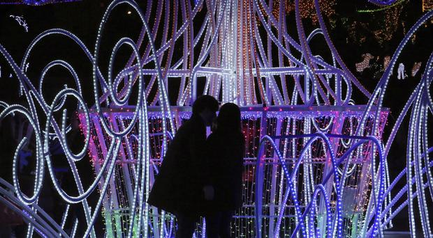 A kissing couple is silhouetted against illuminations celebrating Christmas at Ilsan Lake Park in Goyang, South Korea (AP)