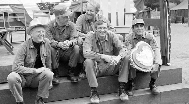 William Christopher, far left, pictured with M*A*S*H co-stars Harry Morgan, Mike Farrell, Alan Alda, and Jamie Farr in 1982 (AP)
