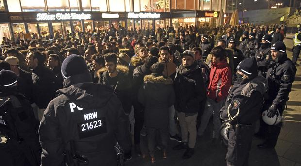 Police officers surround a group of men in front of the main station in Cologne (dpa/AP)