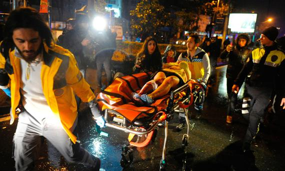 First responders wheel an injured woman away outside the Istanbul nightclub where people were killed while celebrating the New Year