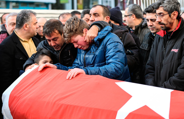 Relatives mourn at the coffin of Ayhan Arik, one of the 39 victims