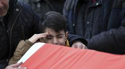 A boy grieves during funeral prayers for Ayhan Akin, one of the nightclub victims, in Istanbul (AP)