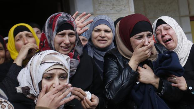 Palestinians cry during the funeral of a man who was killed by Israeli security forces after an alleged stabbing attack in the West Bank in November 2016 (AP)