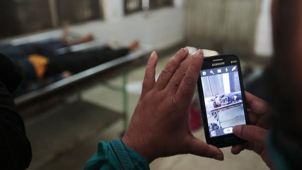 A security officer takes photographs of the bodies of suspected militants at a morgue in Dhaka (AP)