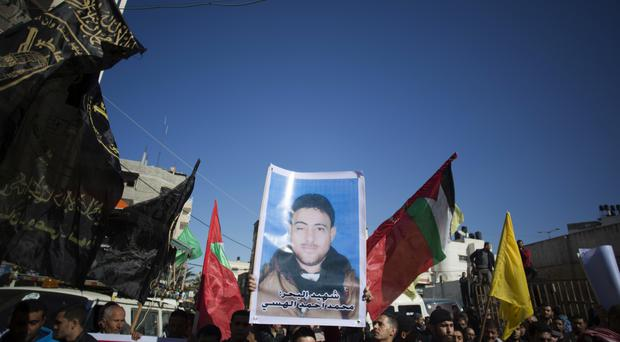 Palestinians hold up a poster of a missing fisherman, Mohammed Al-Hissi, 33, as they attend his symbolic funeral in Gaza City, on Saturday (AP Photo/Khalil Hamra)