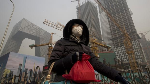 A woman wears a mask as she walks past a construction site as smog continues to choke Beijing (AP/Ng Han Guan)