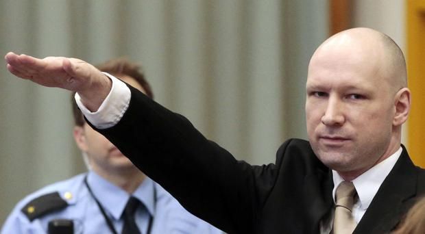 Anders Behring Breivik gestures as he enters a courtroom in Skien, Norway (Lise Aserud, NTB Scanpix via AP)