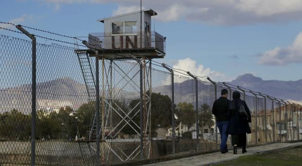 A couple walk past a UN guard post at the fence that divides the Greek and Turkish Cypriots areas. (AP/Petros Karadjias)
