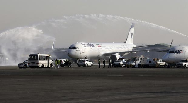 A traditional water cannon salute welcomes Iran Air's new Airbus plane at Mehrabad airport in Tehran (Vahid Salemi/AP)